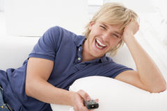 Man in living room holding remote control Stock Photos