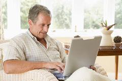 Man in living room with laptop Stock Photography