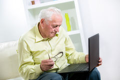 Man in living room with laptop Stock Images