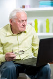 Man in living room with laptop Stock Photos