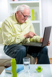 Man in living room with laptop Royalty Free Stock Photography