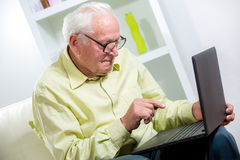 Man in living room with laptop Stock Image