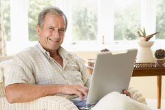 Man in living room with laptop smiling Stock Photography