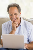 Man in living room with laptop smiling Royalty Free Stock Photos