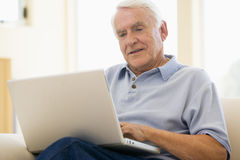 Man in living room with laptop smiling Stock Image