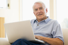 Man in living room with laptop smiling Royalty Free Stock Photo