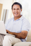 Man in living room with laptop smiling Royalty Free Stock Image