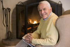 Man in living room with newspaper smiling Stock Photos