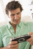 Man in living room playing handheld videogame Stock Photo