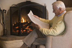 Man in living room reading newspaper stock photo
