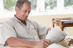 Man in living room reading newspaper smiling Stock Image