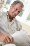 Man in living room reading newspaper smiling Stock Photo