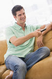 Man in living room with remote control Stock Image