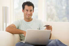 Man in living room using laptop Stock Images