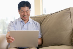 Man in living room using laptop Stock Image