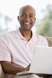Man in living room using laptop Stock Photography