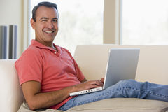 Man in living room using laptop Stock Photos