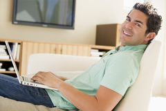 Man in living room using laptop Royalty Free Stock Images