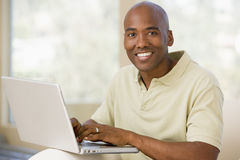 Man in living room using laptop and smiling Royalty Free Stock Image