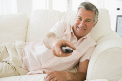 Man in living room using remote control smiling Stock Images