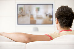 Man in living room watching television Stock Photography