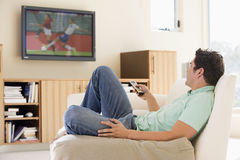 Man in living room watching television Stock Photo