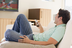 Man in living room watching television Royalty Free Stock Photo