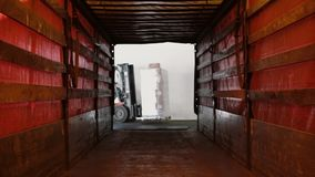 Man on a loader with boxes on it getting into a tunnel in truck. Man on a loader with cardboard boxes on it getting into a tunnel in truck stock footage