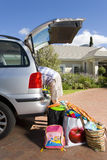 Man loading boot of car with luggage, side view Stock Photography