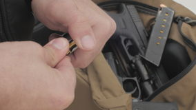 Man Loading Bullets Into a Pistol Magazine. Overhead shot of a man putting bullets into a magazine with various weapons in the background stock video