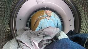 Man loading the the clothes to washing machine. Middle age man wearing glasses loading the the clothes to washing machine. View from the inside of washing stock video footage