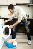 Man loading clothes into the washing machine Royalty Free Stock Photos