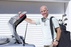 Man loading golf clubs into car trunk Royalty Free Stock Photography