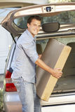 Man Loading Large Package Into Back Of Car Stock Photo