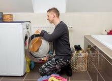 Man loading laundry into washing machine Stock Images