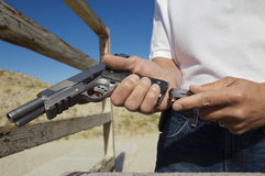 Man Loading Magazine Into Gun At Firing Range Stock Photography