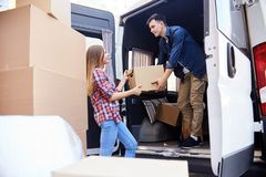 Man  Loading Moving Van. Portrait of young  men loading cardboard boxes to moving van with smiling wife helping him Stock Image