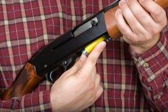 Man loading shotgun. A man inserts a shell into a semiautomatic shotgun Stock Image