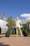 Man loading suitcases into car trunk Stock Images