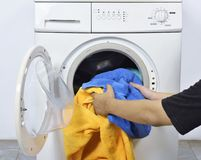 Man Loading The Dirty Towels Into Washing Machine For Washed Royalty Free Stock Image