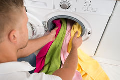 Man Loading Towels Into The Washing Machine Royalty Free Stock Photo