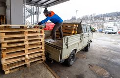 Man is loading wooden pallets on a truck in winter. Stock Photos