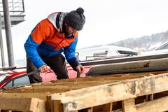 Man is loading wooden pallets on a truck in winter. Stock Images