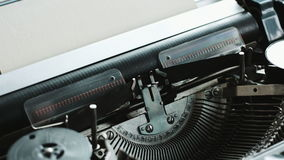 Man loads a blank sheet of paper in the typewriter. Close-up of man hands loads blank sheet of paper in vintage typewriter stock video