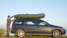 A man loads an inflatable boat onto the roof of the car for transportation. Securely fixes.  stock video footage