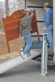 Man loads moving van. Man loads headboard onto moving van, while a second man watches Stock Photography