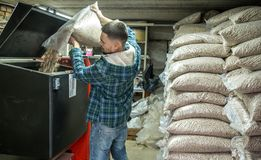 The man loads the pellets in the solid fuel boiler, economical h. The man loads the pellets in the solid fuel boiler, working with biofuels, economical heating Stock Photography
