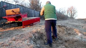 Man loads sand with a shovel into the trailer of the motoblock stock footage