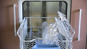 Man loads the tray with the dishes and closes the dishwasher door. stock footage