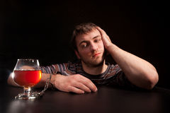 Man locked to glass of alcohol. By handcuffs Stock Photos
